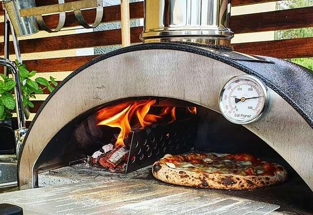 Pizza på väg ut från vedeldade pizzaugnen