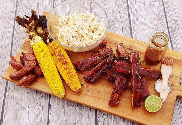 Hot and sticky revbensspjäll serverade på grillbricka med majs och coleslaw