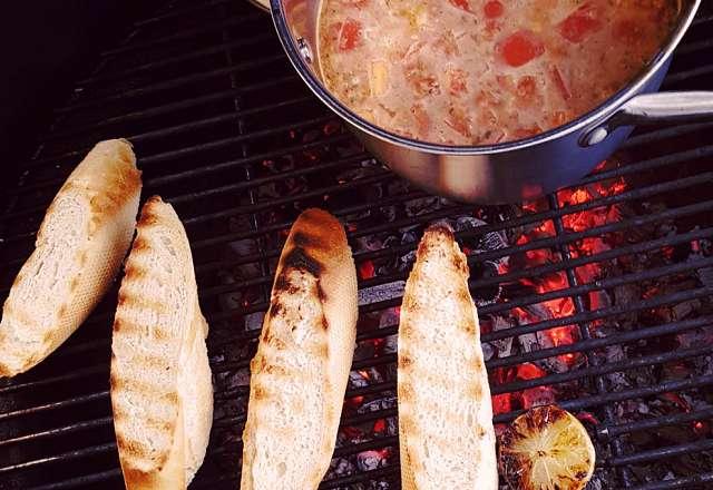 Grillat bröd och kokande thaisoppa på grillen